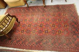 Afghan rug with four rows of twelve gols with multiple borders on wine ground, approximately 84ins x