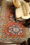 20th Century Turkish carpet of Kazak design with a triple hooked medallion pattern on a terracotta