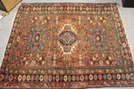 Karaja rug with a triple medallion and all-over stylised design on a rose ground with triple border,