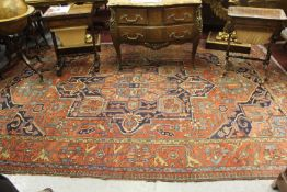 Antique Heriz carpet with a typical medallion and all-over stylised floral design on a brick red
