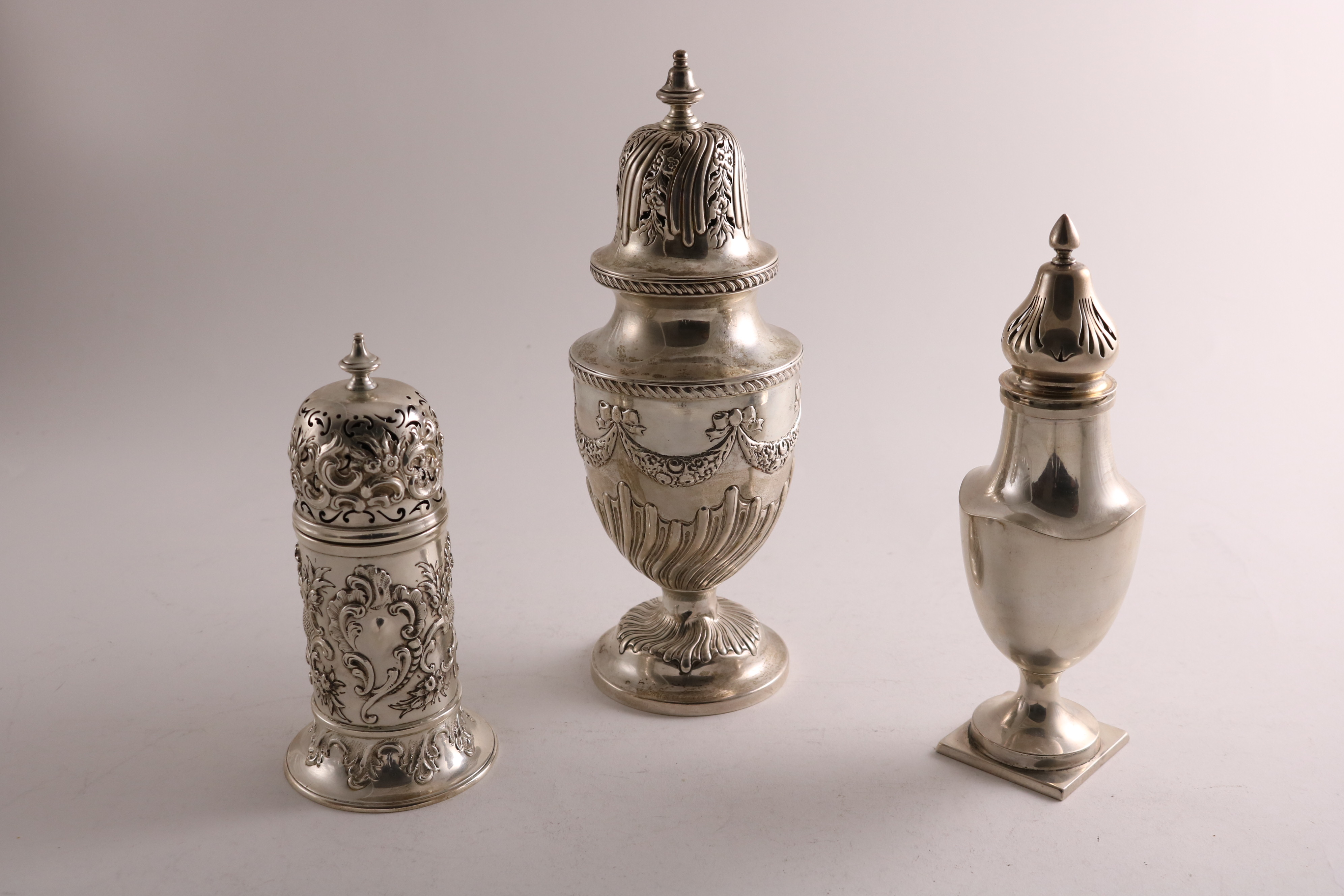 """Lot 46 - THREE SILVER SUGAR CASTERS:- A late Victorian embossed """"lighthouse"""" caster, by Messrs Slater, Slater"""
