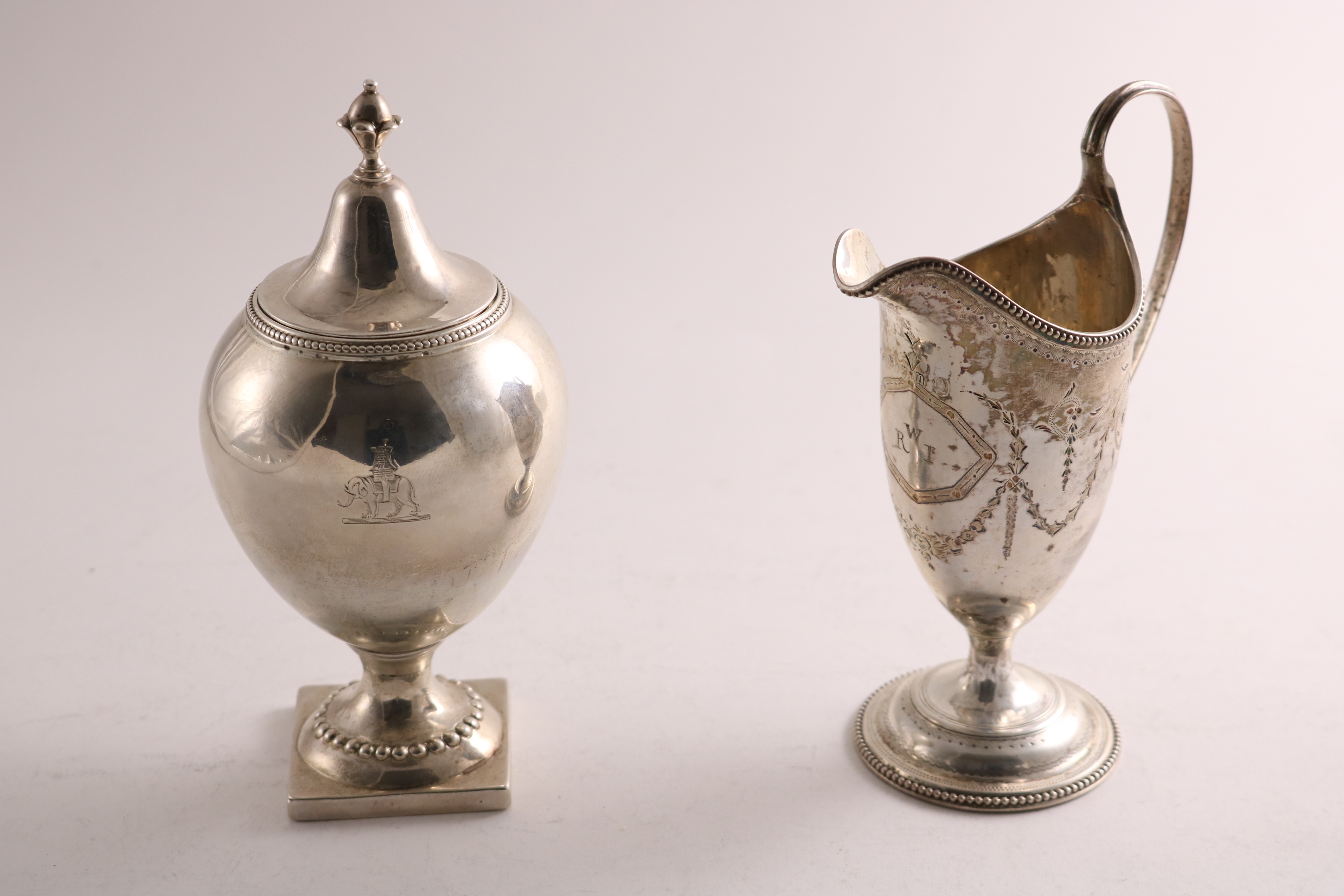 Lot 43 - A GEORGE III SILVER SUGAR VASE with an oviform body, square pedestal foot and bead borders, crested,