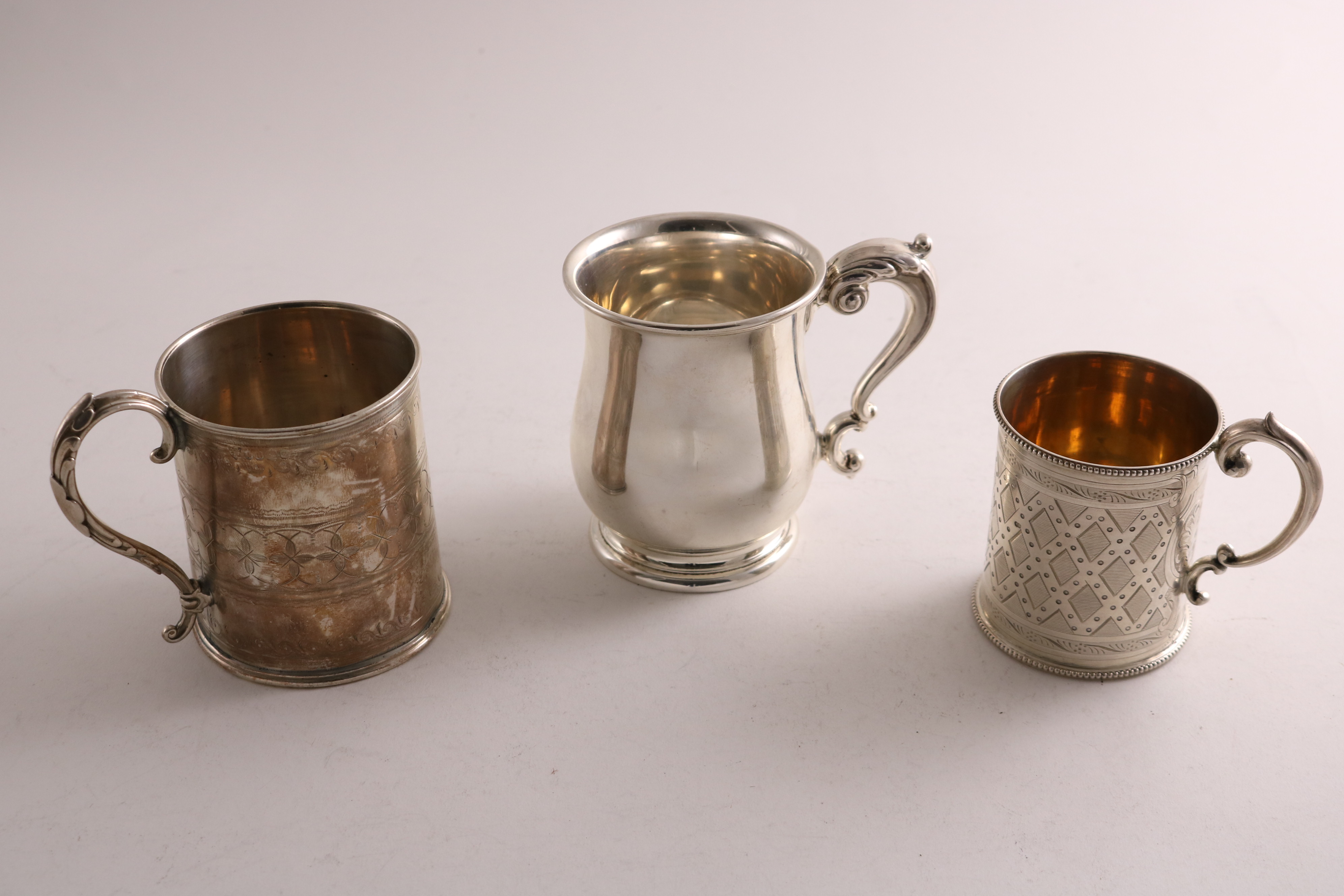Lot 60 - AN EARLY 20TH CENTURY SMALL SILVER MUG of baluster form with a leaf-capped scroll handle, by W.