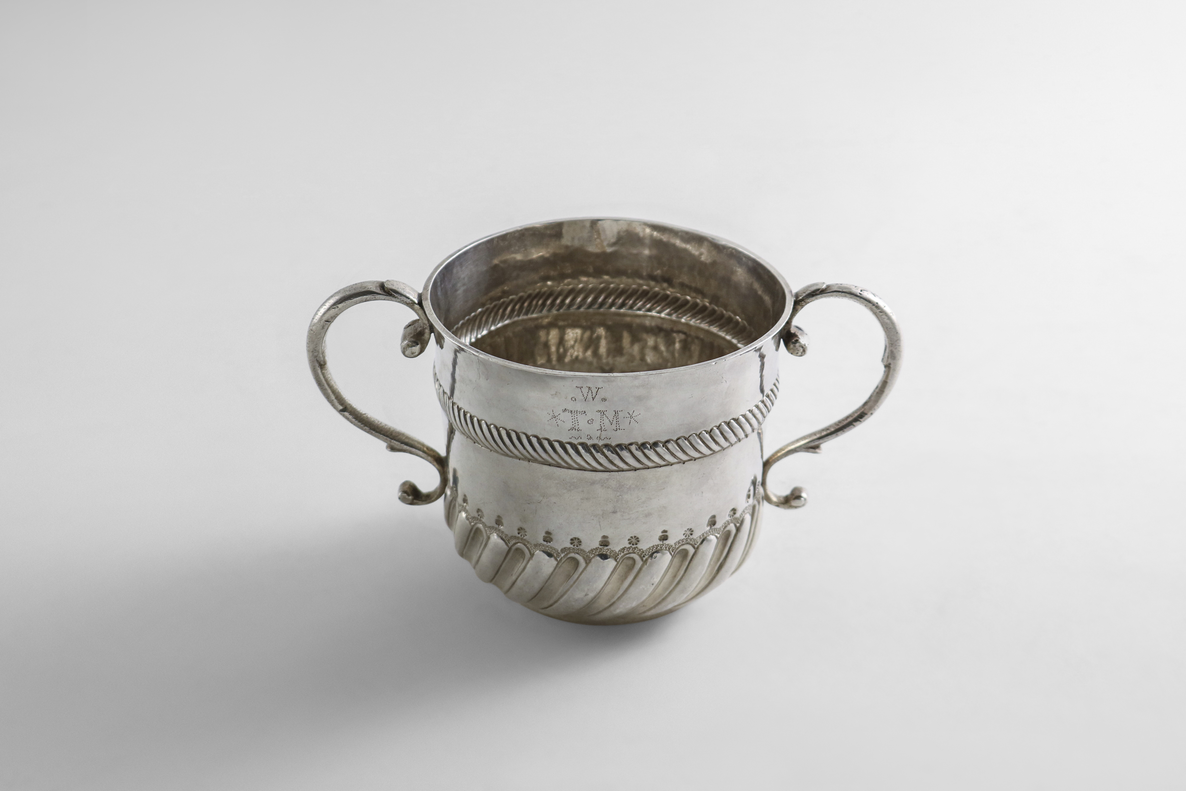 Lot 15 - A WILLIAM & MARY SILVER PORRINGER with two scroll handles, a wrythen-fluted lower body, maker's mark