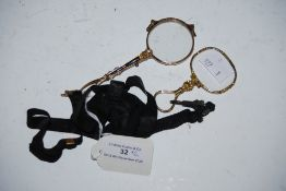 PAIR OF YELLOW METAL LORGNETTES, TOGETHER WITH A YELLOW METAL MAGNIFYING GLASS ON BLACK RIBBON
