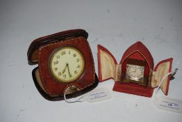 BRASS CASED TRAVELLING TIMEPIECE IN RED VELVET CASE BY HOME WATCH COMPANY, TOGETHER WITH AN EIGHT