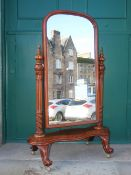A Victorian mahogany cheval mirror, the arched mirror plate enclosed by tapered cylindrical