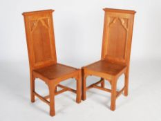 A pair of early 20th century oak Gothic presentation altar chairs, the rectangular panelled backs