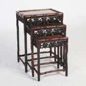 A nest of three Chinese dark wood occasional tables, late 19th/early 20th century, the rectangular