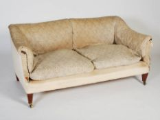 A late 19th/early 20th century mahogany sofa by Howard & Sons, the upholstered back, arms and