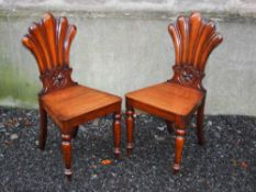 A pair of 19th century mahogany fan back hall chairs, the fan shaped backs carved with floral