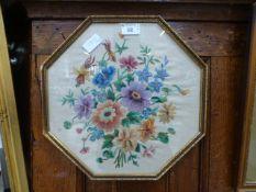 An octagonal framed and glazed needlewor