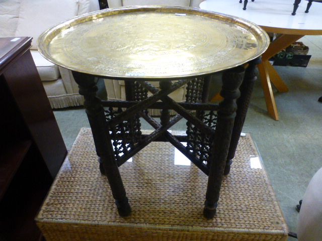 Lot 112 - An engraved circular brass tray on carve
