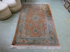A handwoven Persian style rug, the peach
