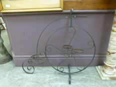 A wrought metal plant pot holder in the