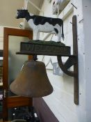 A cast metal wall hanging bell with cow