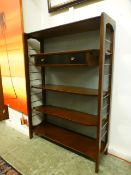 A mid-20th century open bookcase with ad