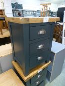 An oak topped and dark grey based three drawer bedside cabinet (16.