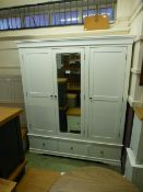 An ivory triple wardrobe with drawer base (17.