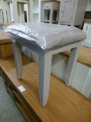 A grey stool with upholstered feet (2.