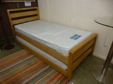 A modern single bed with pull out bed underneath and two mattresses