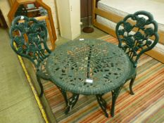 A cast aluminium and green painted bistro set