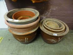 A selection of earthenware and terracotta plant pots some being glazed