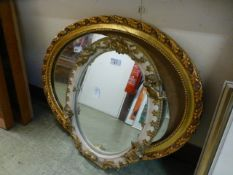 Two ornate framed oval mirrors