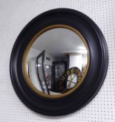CIRCULAR CONVEX MIRROR, Regency style with a circular ebonised frame with reeded gilt border,