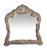 A VICTORIAN EMBOSSED SILVER MOUNTED DRESSING TABLE MIRROR with shaped and bevelled glass, 34cm