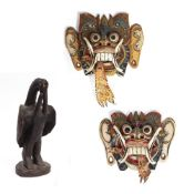 A PAIR OF MID 20TH CENTURY PAINTED INDONESIAN DRAGON FACE MASKS each 25cm wide x 22cm high and a