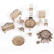 A GROUP OF FILIGREE WHITE METAL MINIATURE FURNITURE to include a pair of settees, a dining table,
