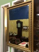 A CONTEMPORARY GILDED PINE FRAMED RECTANGULAR WALL MIRROR with bevelled glass, 76.5cm x 106cm
