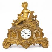 A 19TH CENTURY FRENCH GILT METAL MANTLE CLOCK adorned with a cherub, the enamelled dial signed '