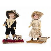 A PAIR OF VICTORIAN DOLLS a boy and a girl, each dressed in period costume and mounted on a