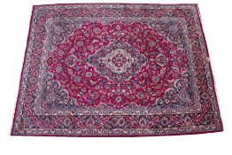 A MIDDLE EASTERN MASHAD HAND KNOTTED WOOLLEN CARPET with classic floral decoration and a central