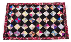 A RECTANGULAR PATCHWORK BEDCOVER OR HANGING with geometric diamond shaped motifs within a rose