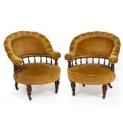 A PAIR OF LATE VICTORIAN WALNUT FRAMED UPHOLSTERED TUB CHAIRS with turned legs terminating in