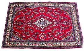 A MIDDLE EASTERN HAMADAN RED GROUND CARPET with a floral decoration, a central medallion and ivory