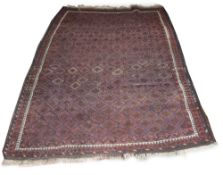 AN EASTERN RUG woven with a multitude of hooked medallions on a maroon ground, 164cm x 126cm At