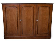A VICTORIAN MAHOGANY TRIPLE WARDROBE with three panelled doors opening to reveal linen slides, a