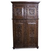 A 20TH CENTURY 17TH CENTURY STYLE CARVED OAK CUPBOARD with panel doors opening to reveal linen