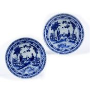 Two blue and white chargers Chinese, 19th Century depicting figures in a garden sat at a table, with