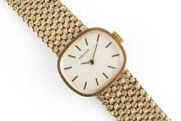 A LADY'S 9CT GOLD BRACELET WATCH BY TISSOT, the cushion-shaped dial with baton markers, to a