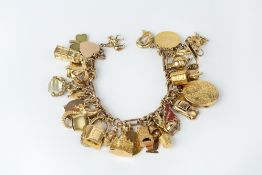 A CHARM BRACELET, the yellow precious metal fancy-link bracelet suspending a collection of