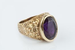 AN AMETHYST SINGLE STONE RING, the oval mixed-cut amethyst collet set to a tapered hoop with