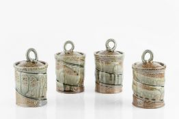 Walter Keeler (b.1942) A set of four cylindrical pots and covers with dripped green glaze over ash