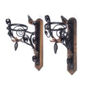 Arts & Crafts A pair of wall brackets painted cast iron and copper with later wooden brackets 45cm