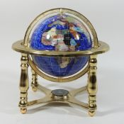 A polished hardstone terrestrial table globe on a brass mount,