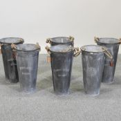 A set of six circular galvanized tall metal planters,